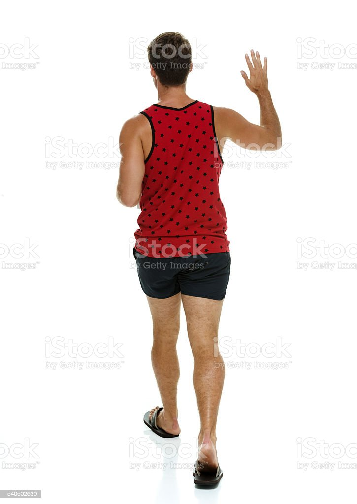 Rear view of casual man waving hand stock photo