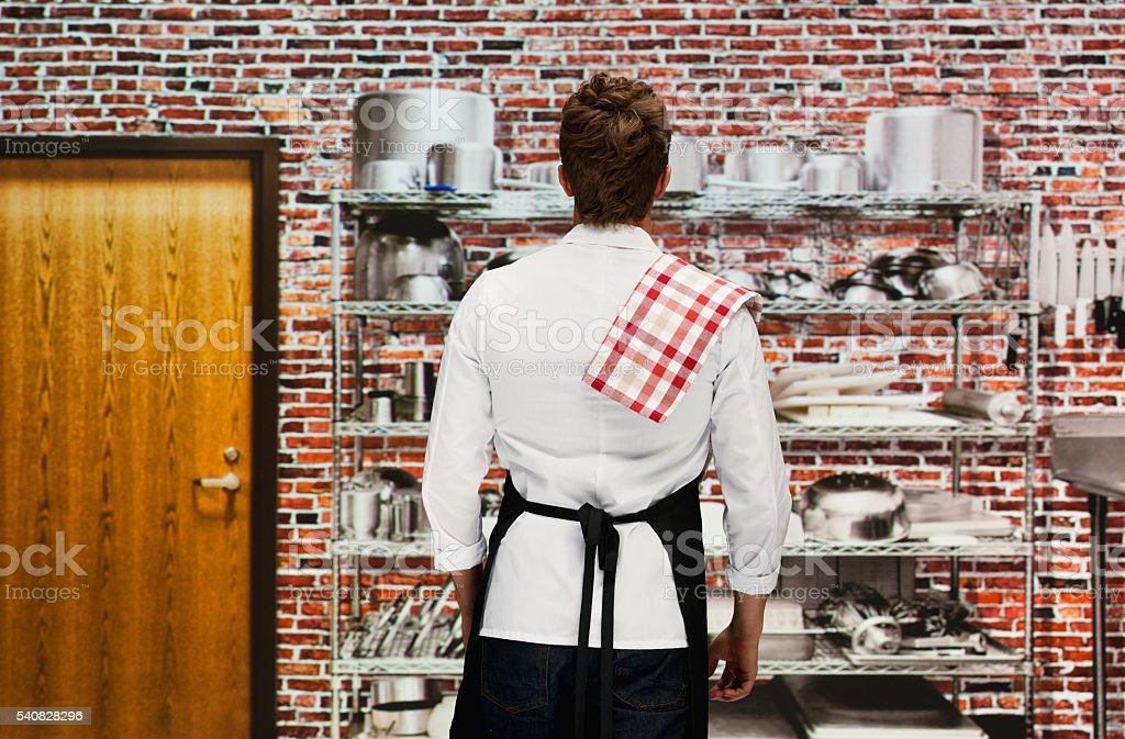 Rear view of chef standing in kitchen stock photo
