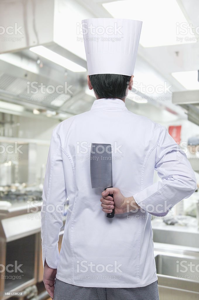 Rear View of Chef with Knife Behind his Back royalty-free stock photo