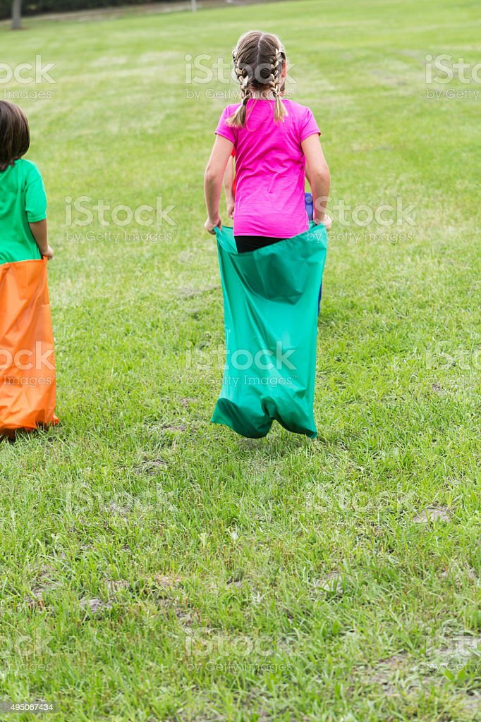 Rear view of children in sack race stock photo