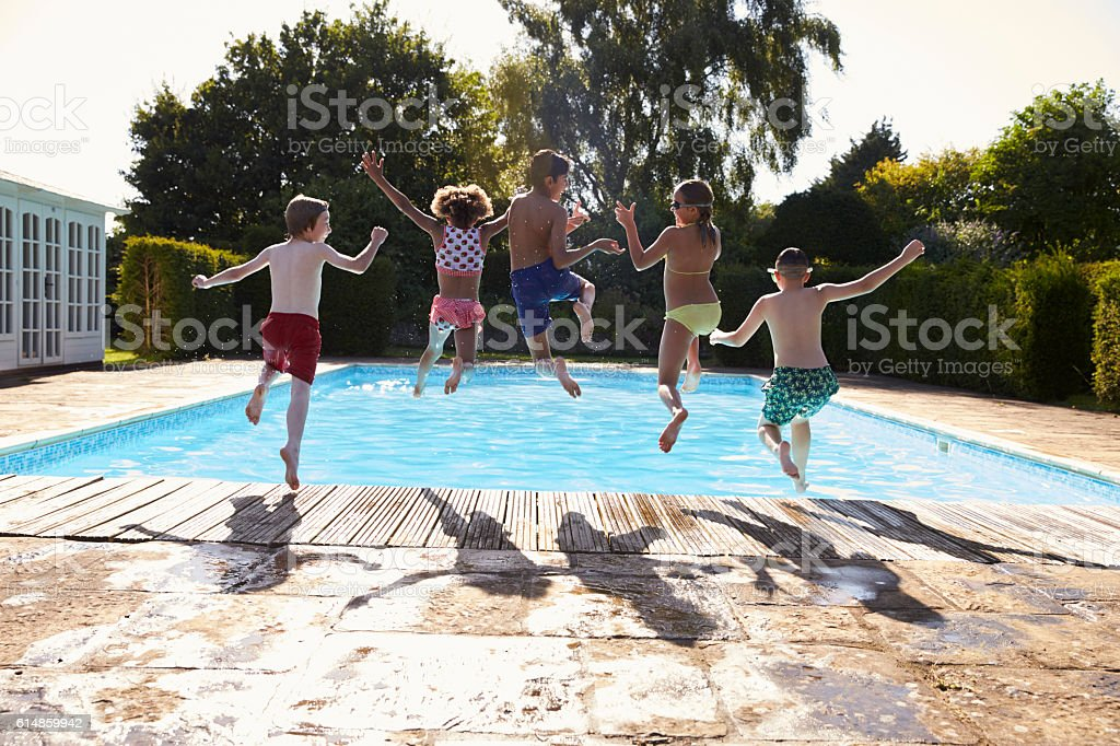 Rear View Of Children Jumping Into Outdoor Swimming Pool stock photo