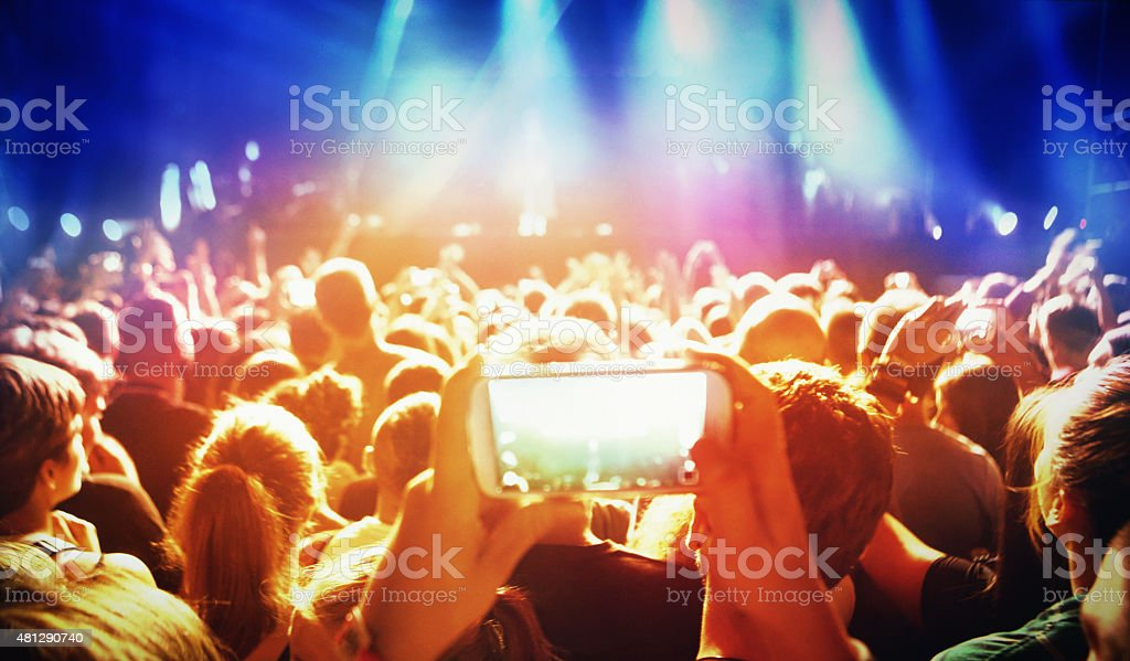 Rear view of concert crowd taping the show. stock photo