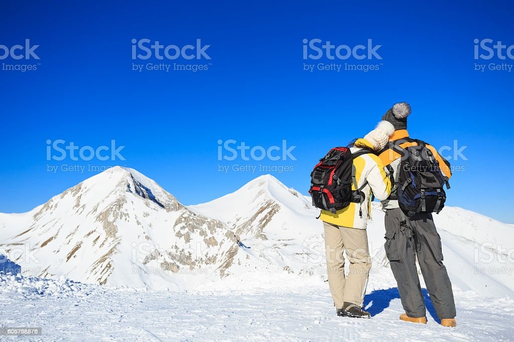 Rear view of couple backpackers hiking in the snow mountain stock photo