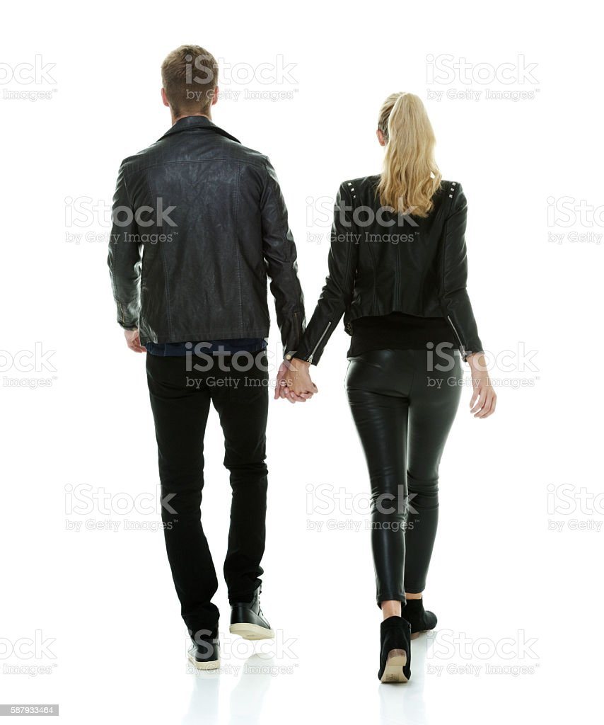 Rear view of couple holding hands and walking stock photo