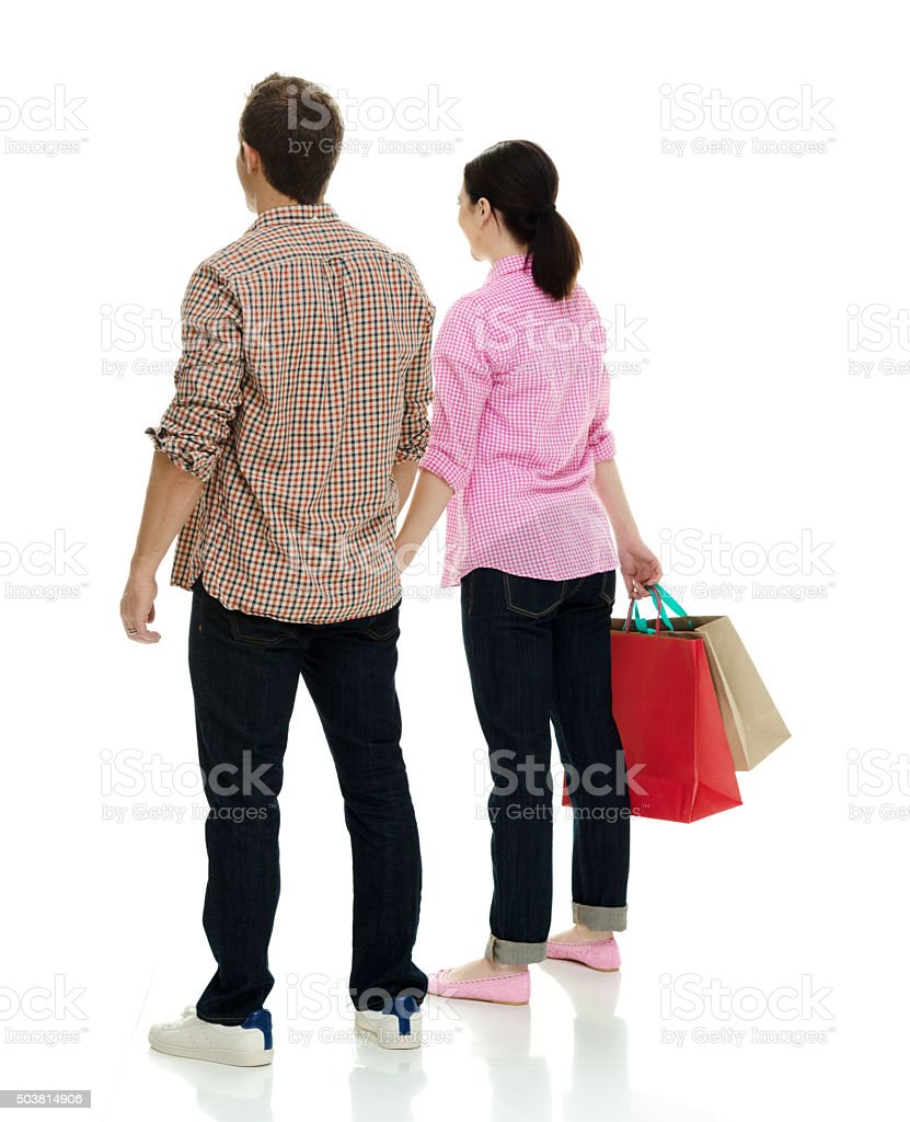 Rear view of couple holding shopping bag stock photo