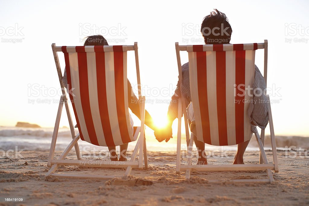 Rear view of couple in deck chairs on beach royalty-free stock photo