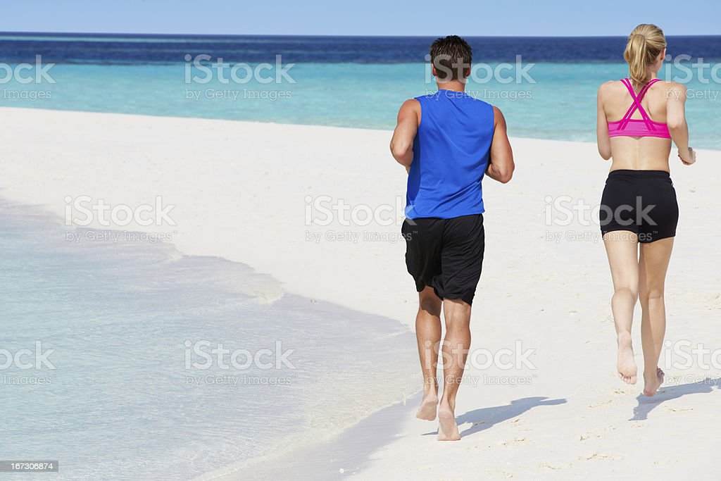 Rear View Of Couple Running On Beautiful Beach royalty-free stock photo