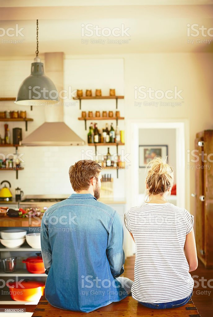 Rear view of couple sitting on trunk in kitchen stock photo