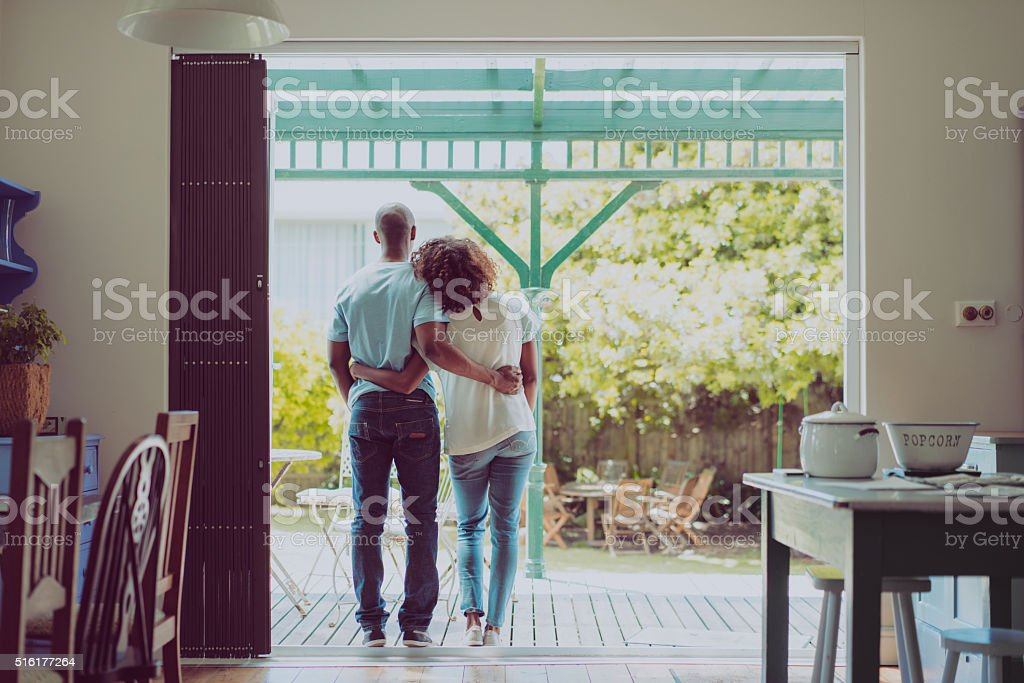 Rear view of couple standing arms around at entrance stock photo