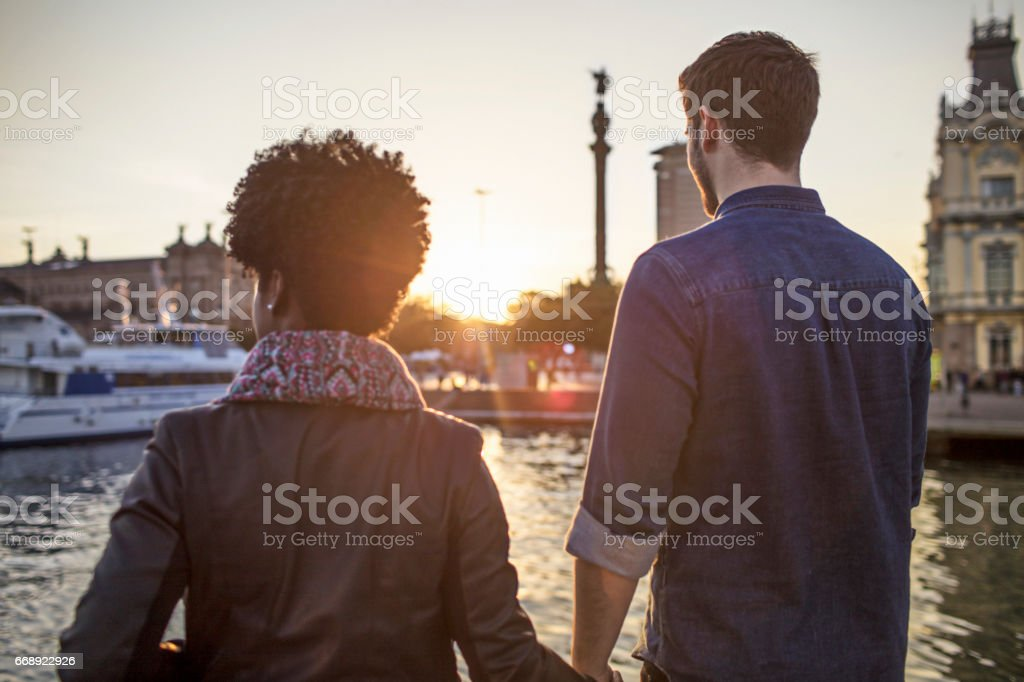 Rear view of couple standing at harbor in city stock photo