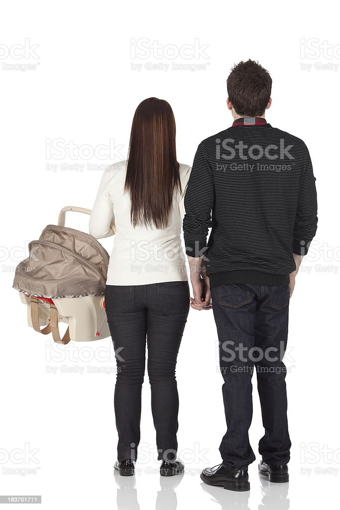Rear view of couple standing with a baby carrier royalty-free stock photo