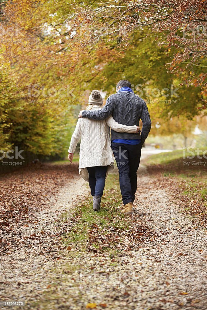 Rear View Of Couple Walking Along Autumn Path royalty-free stock photo