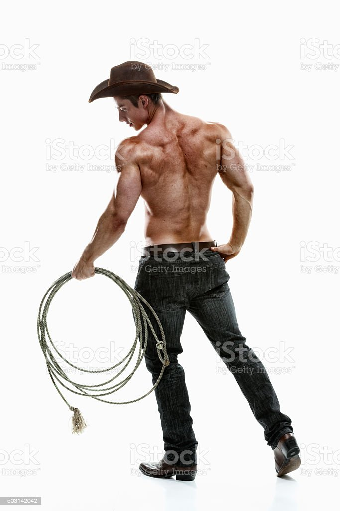 Rear view of cowboy holding lasso stock photo