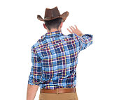 Rear view of cowboy waving hand