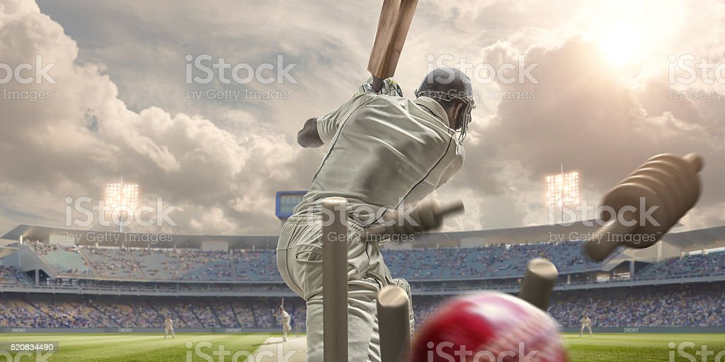 Rear View Of Cricket Ball Hitting Stumps Behind Batsman stock photo