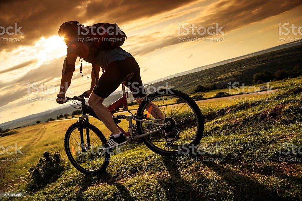 Rear view of cyclist climbing the mountain stock photo