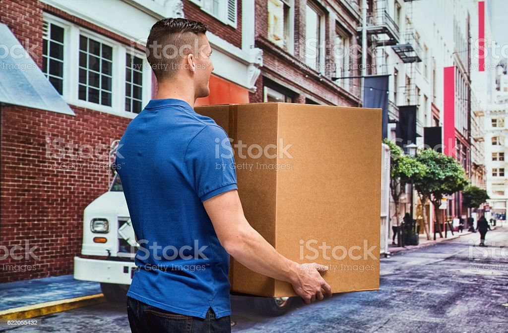 Rear view of delivery person holding box outdoors