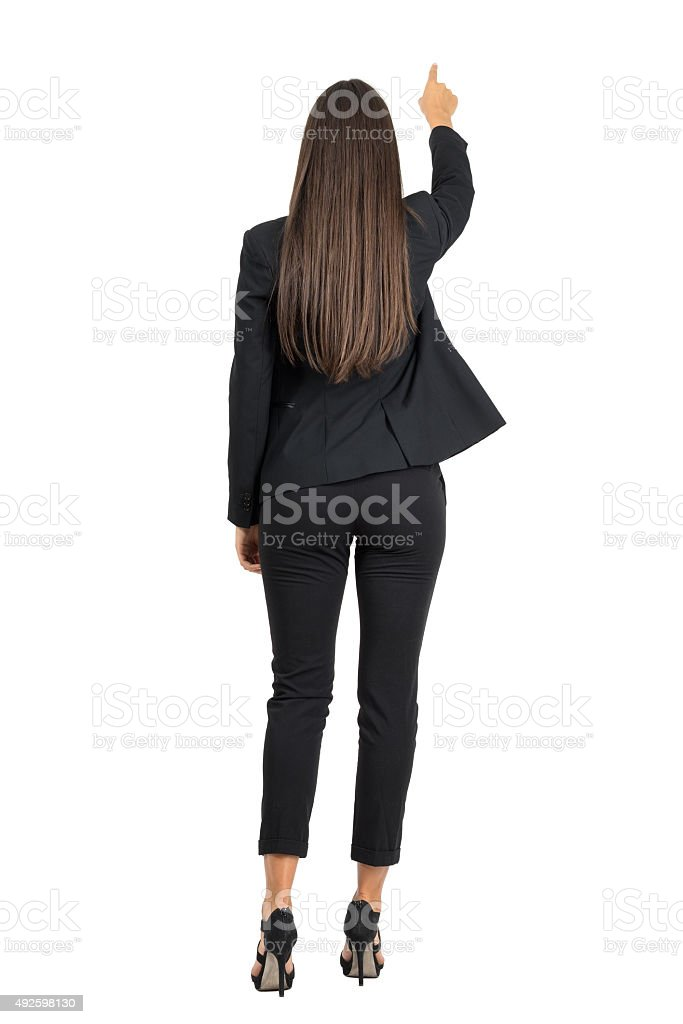 Rear view of elegant businesswoman pointing in front of her stock photo