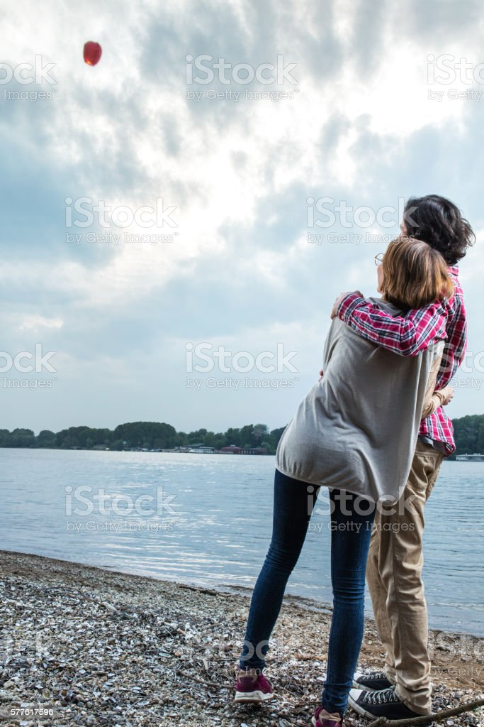 Rear view of embraced couple looking at sky lantern. stock photo