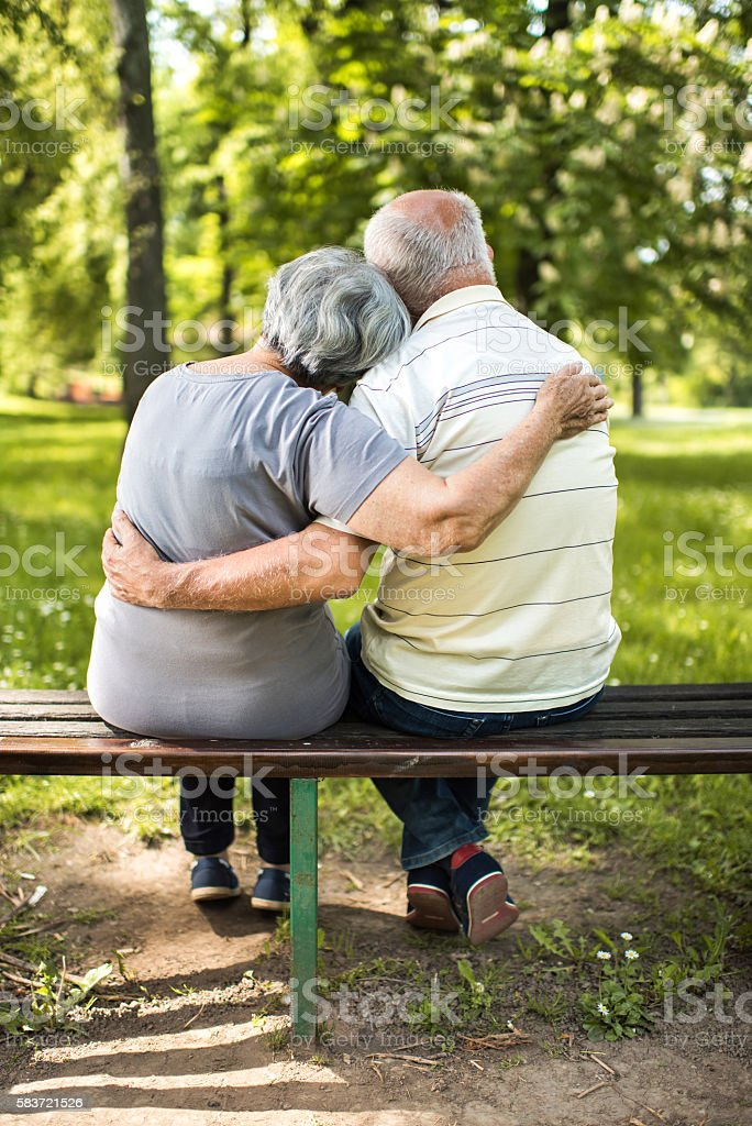 Rear view of embraced couple relaxing on a bench. stock photo
