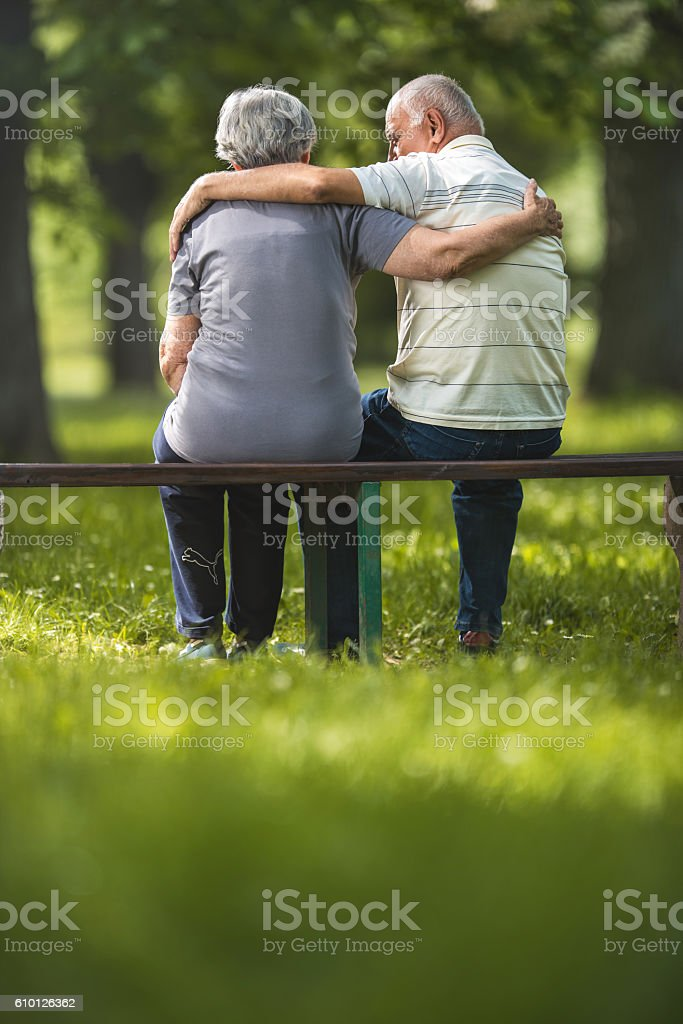 Rear view of embraced senior couple relaxing on a bench. stock photo
