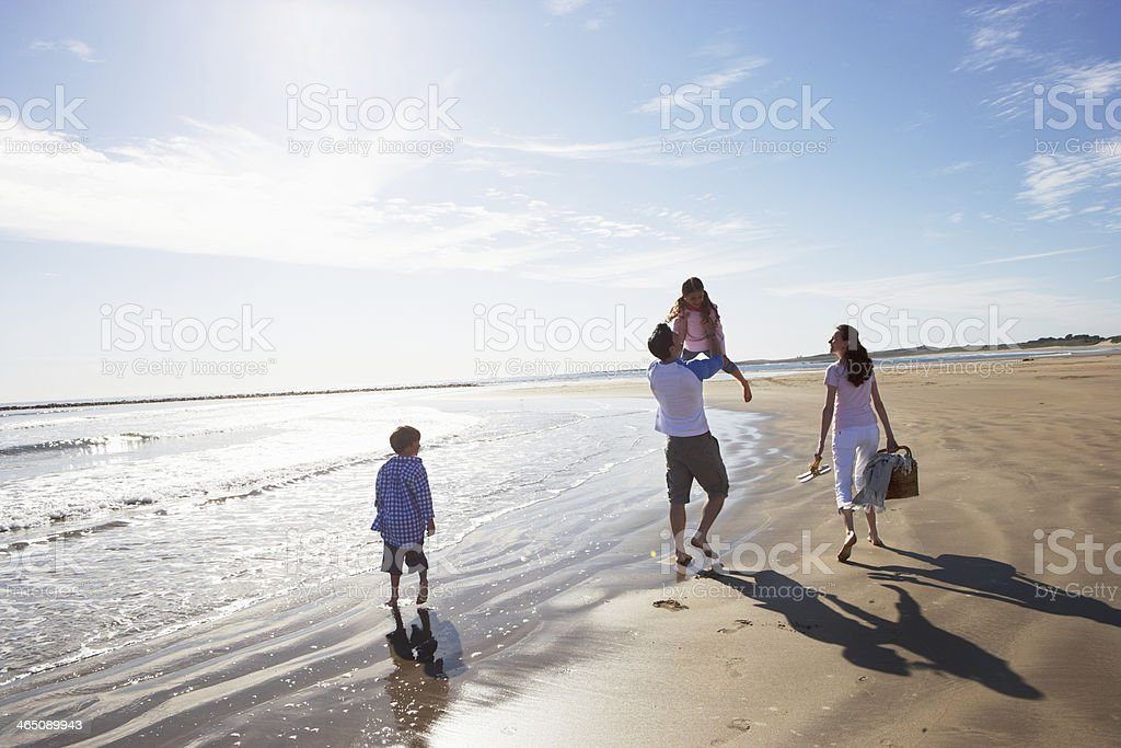 Rear View Of Family Walking Along Beach With Picnic Basket stock photo