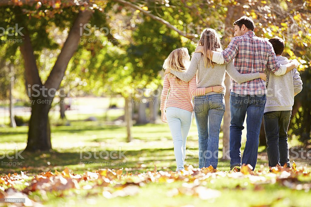 Rear View Of Family Walking Through Autumn Woodland stock photo