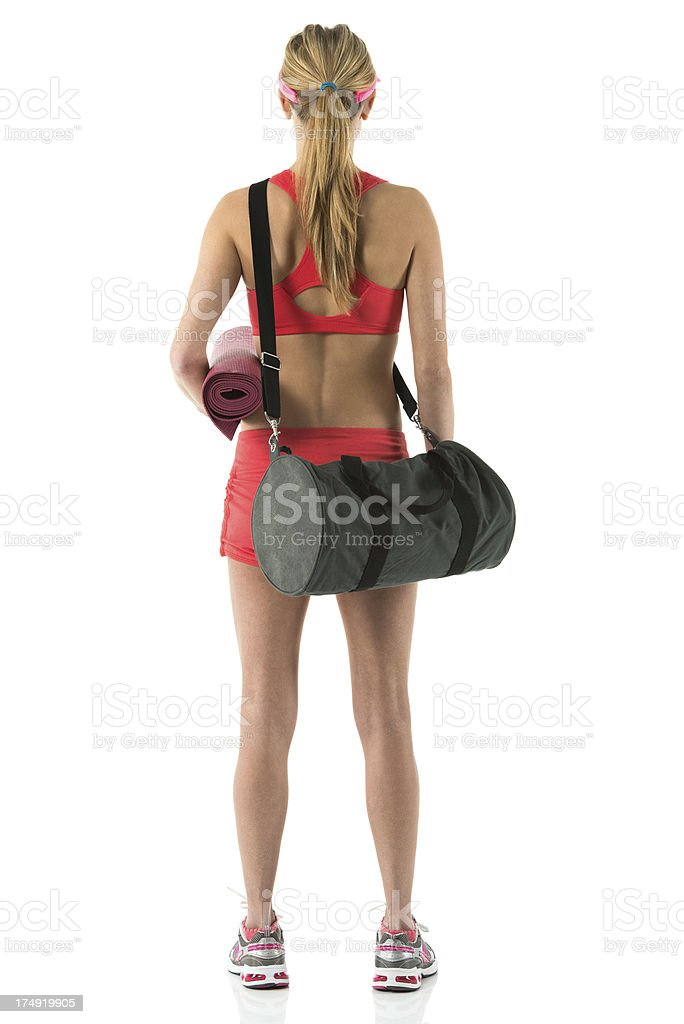 Rear view of female athlete with exercise mat and bag royalty-free stock photo