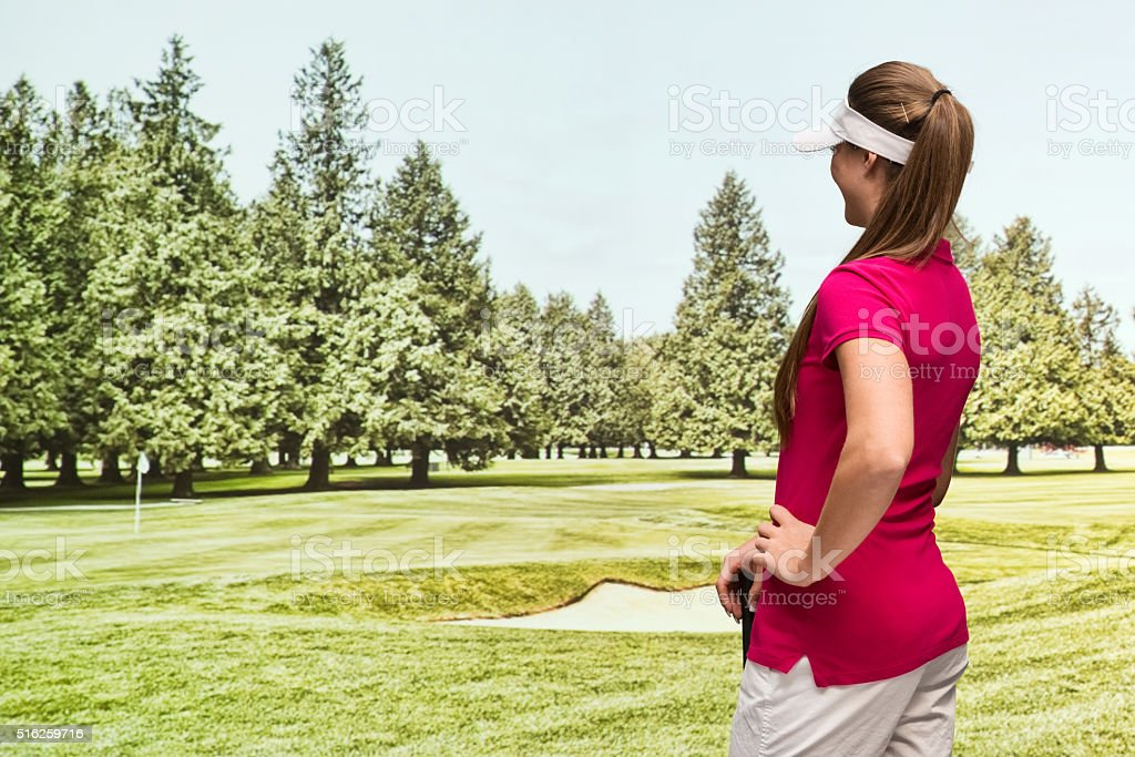 Rear view of female golfer in the field stock photo