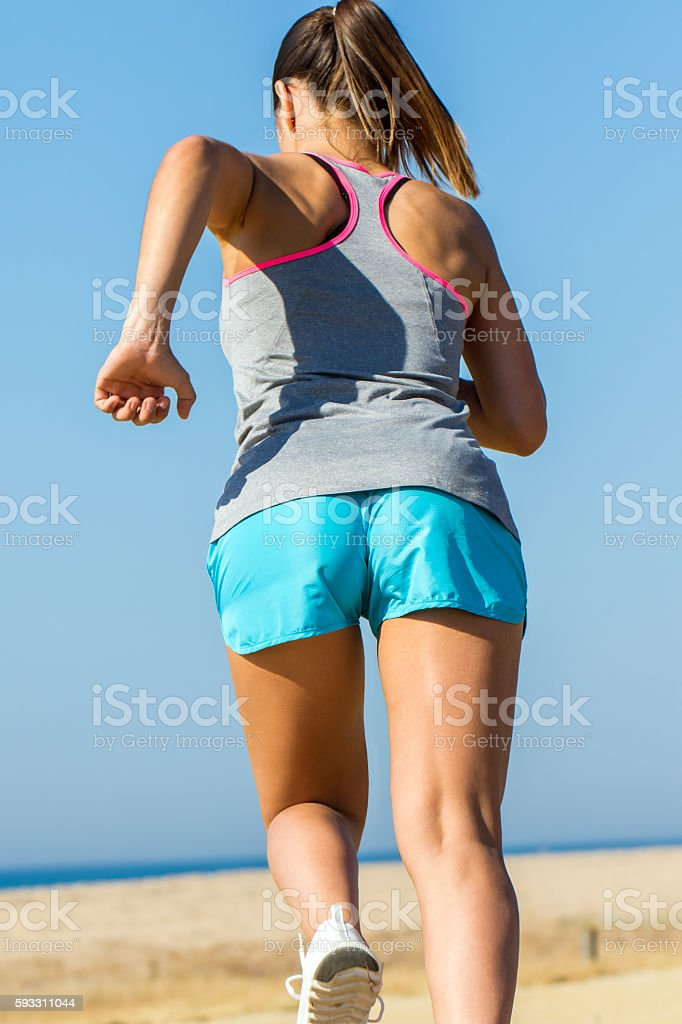 Rear view of female runner in action. stock photo