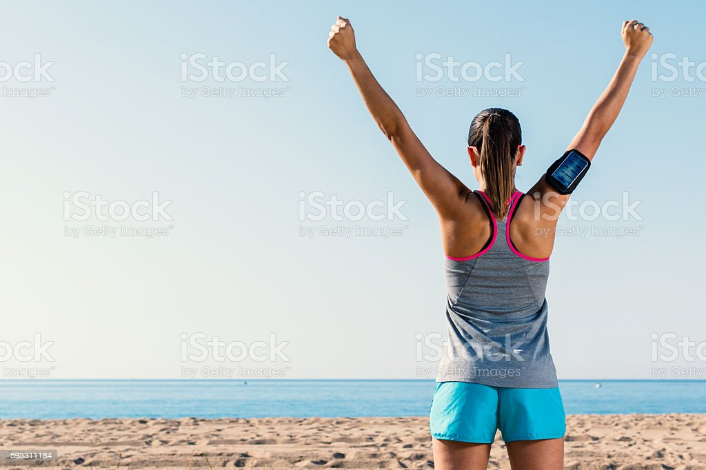 Rear view of female runner raising arms. photo libre de droits