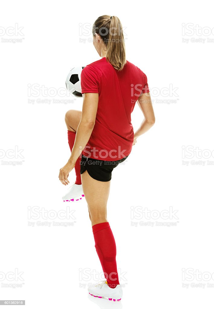 Rear view of female soccer player juggling stock photo