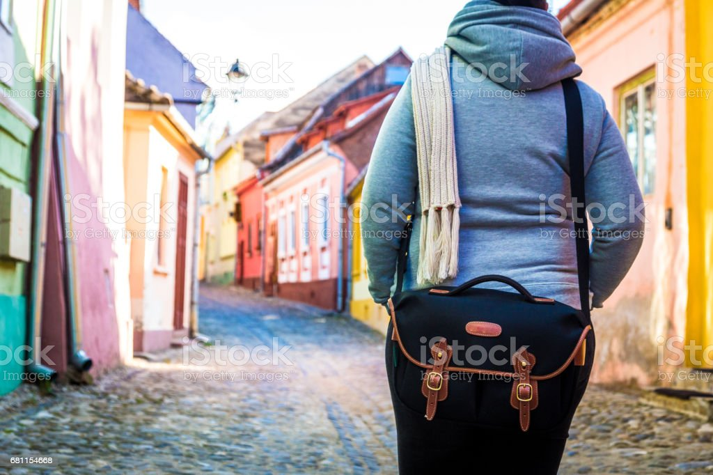 Rear view of female traveler wearing black shoulder bag with colourful houses blurred in the background stock photo