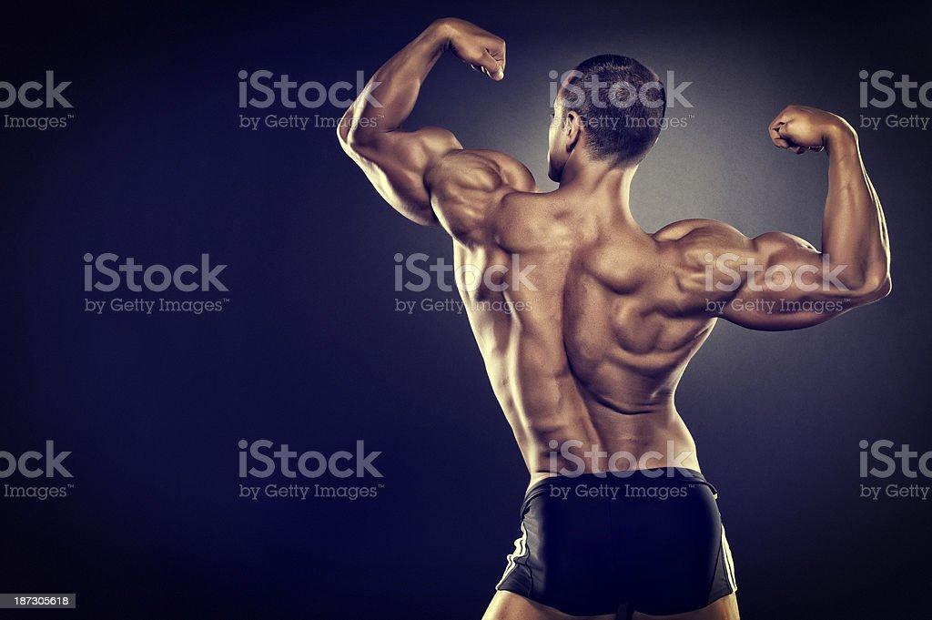 Rear view of flexing muscular man stock photo