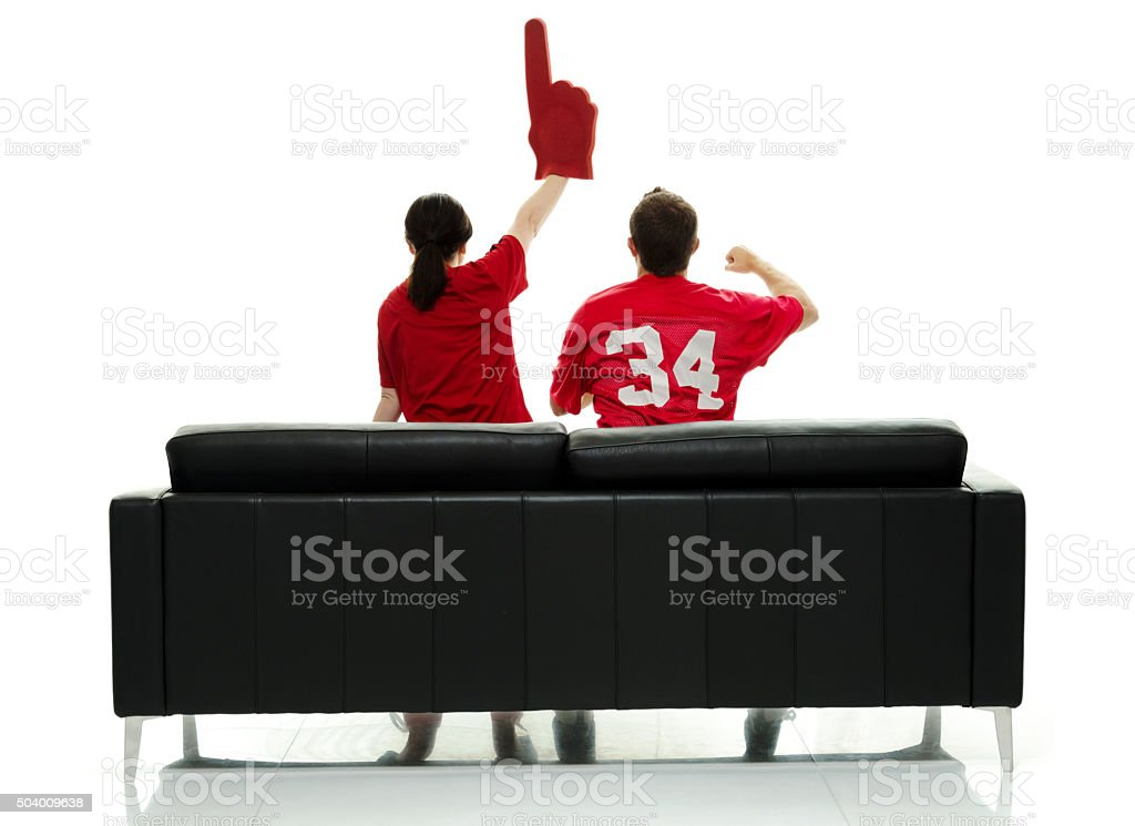 Rear view of football fans on couch and cheering stock photo