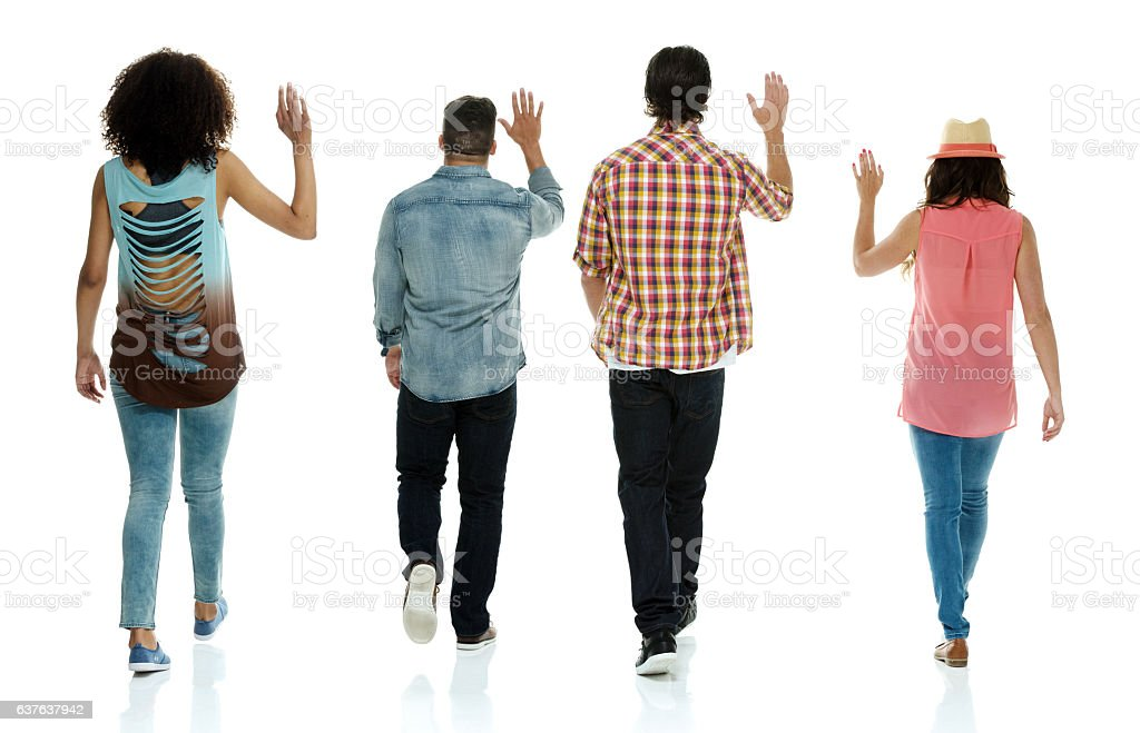Rear view of four friends walking and waving hand stock photo