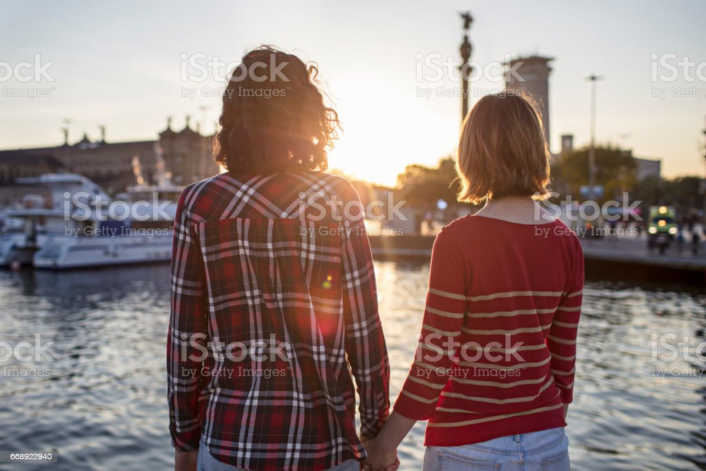 Rear view of friends holding hands at port stock photo