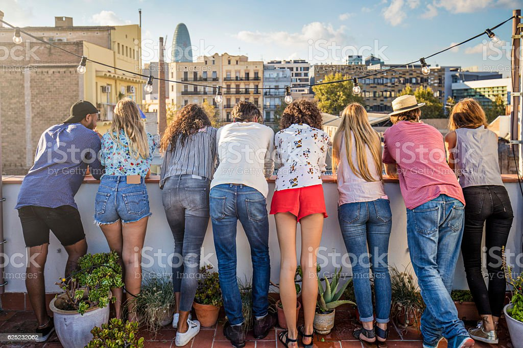 Rear view of friends standing together on terrace stock photo