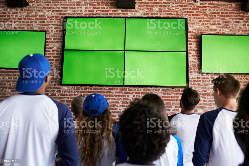Rear View Of Friends Watching Game In Sports Bar On stock photo