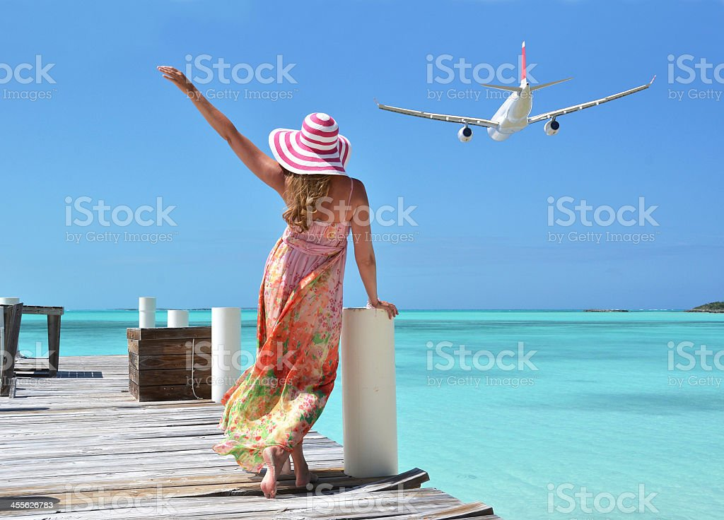 Rear view of girl in floppy beach hat standing on pier stock photo