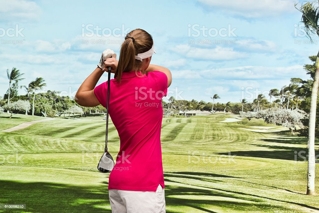 Rear view of golfer swinging at the field stock photo