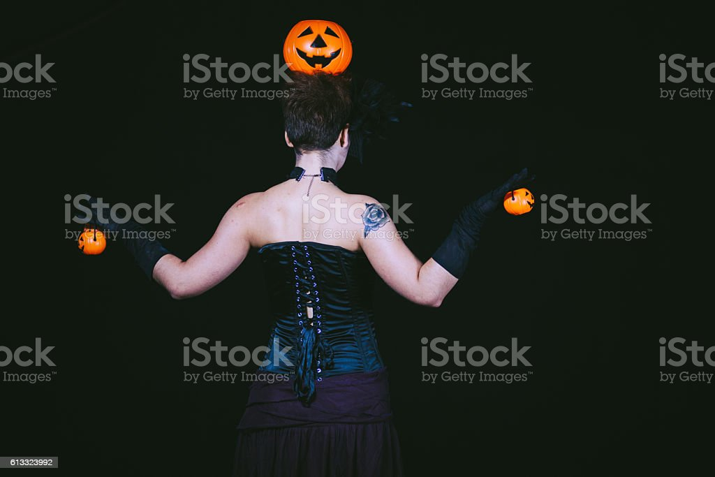 Rear View of Goth Girl Holding Pumpkins stock photo