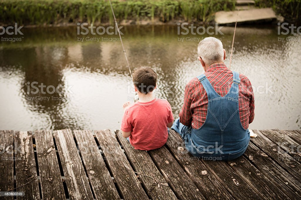 Rear View of Grandpa Fishing With His Great Grandson stock photo