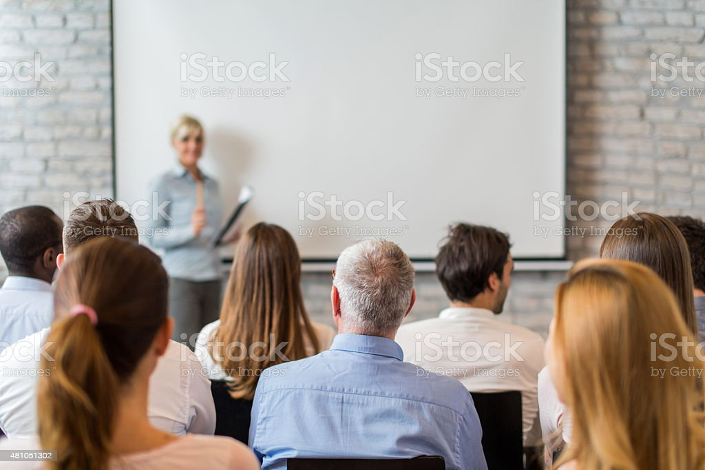 Rear view of group of business people on education event. stock photo