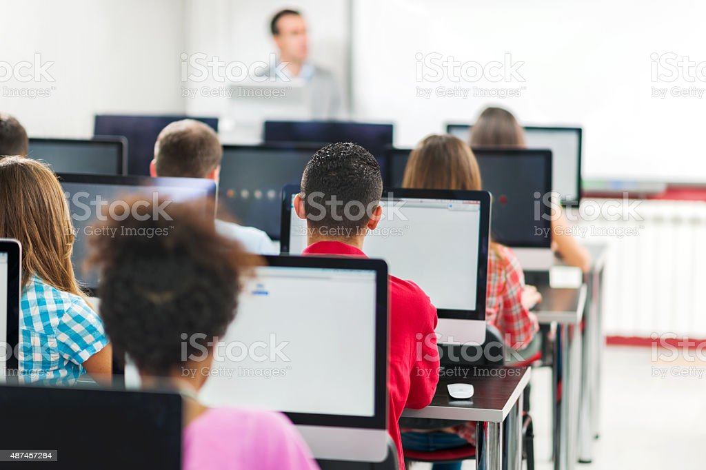 Rear view of group of people in a computer lab. stock photo