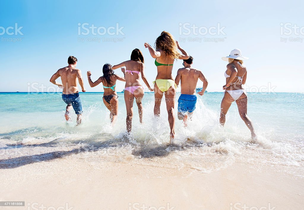 Rear view of group of people running into sea. stock photo
