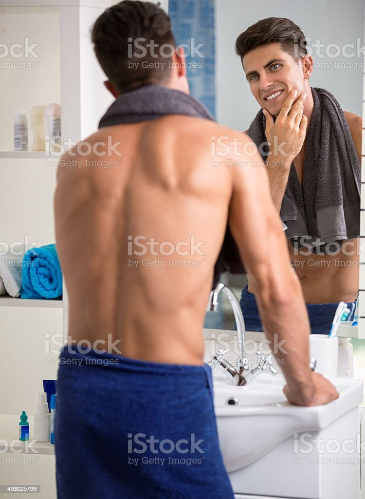 Rear view of handsome young standing against a mirror stock photo