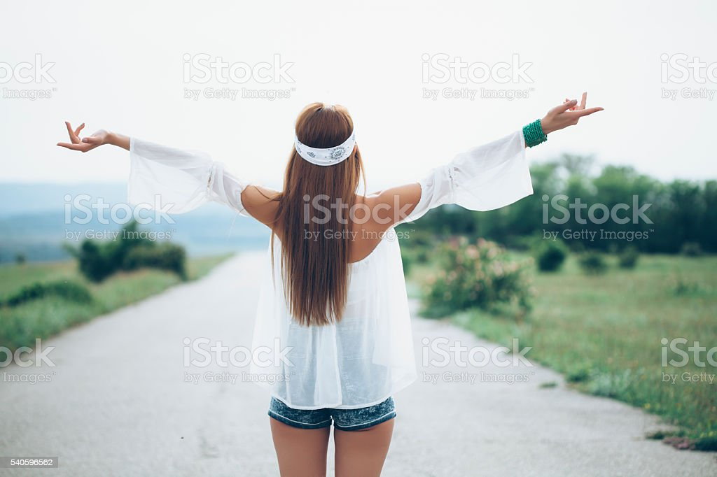 Rear view of happy young woman standing on the road stock photo