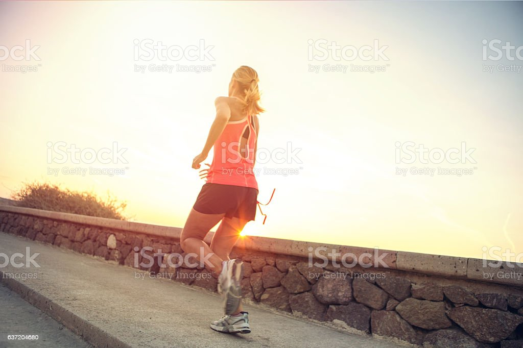 Rear view of healthy and sporty young woman running outdoors stock photo