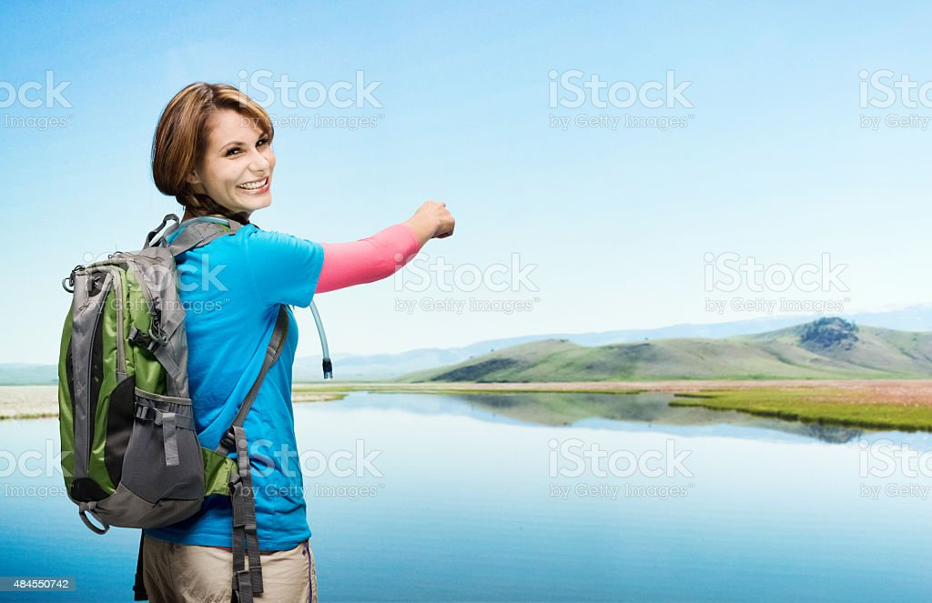 Rear view of hiker pointing at nature stock photo